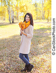 Beautiful smiling woman with yellow maple leafs in autumn day