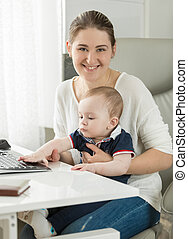 Beautiful smiling woman working on computer with her baby son