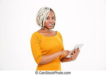 Beautiful smiling young african american woman using tablet