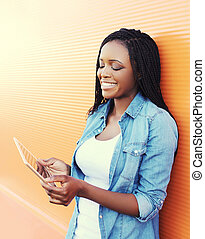 Beautiful smiling young african woman using tablet pc in city