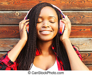 Beautiful smiling young african woman with headphones is enjoying listens to music