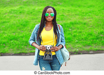 Beautiful smiling young african woman with retro vintage camera in city park