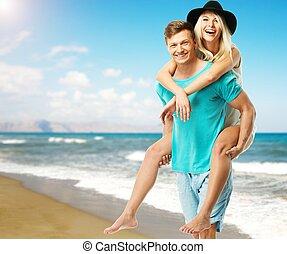 Beautiful smiling young couple having fun on a beach