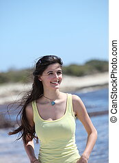 Beautiful smiling young woman at the seaside