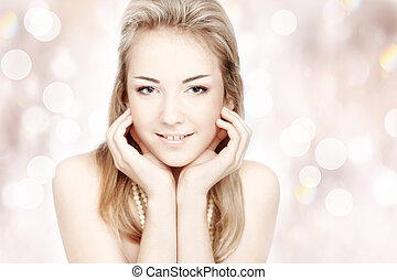 Beautiful smiling young woman. Closeup portrait over abstract shiny background