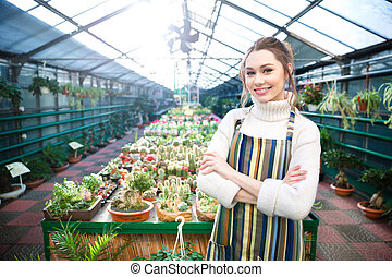 Beautiful smiling young woman gardener standing near cactuses