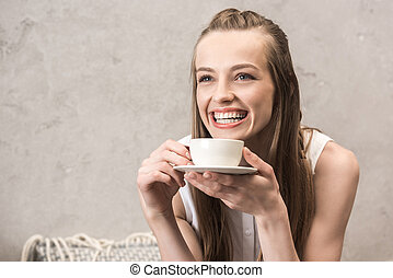 Beautiful smiling young woman holding coffee cup and looking away