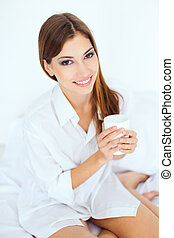 young woman in bed with a cup of coffee
