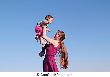 Beautiful smiling young woman in pink dress holding her son