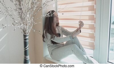 Beautiful smiling young woman is played by roller blinds. The girl is sitting on the windowsill.