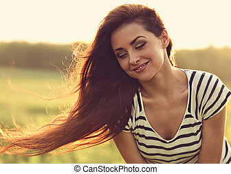 Beautiful smiling young woman looking happy with long amazing bright hair on nature bright sunset summer background. Closeup toned portrait