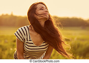 Beautiful smiling young woman looking happy with long amazing bright long hair on nature bright sunset summer background. Closeup toned color portrait.