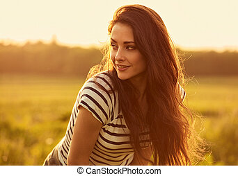 Beautiful smiling young woman looking happy with long amazing bright long hair on nature bright sunset summer background. Closeup