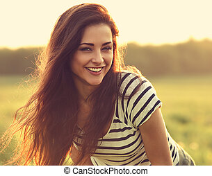 Beautiful smiling young woman looking happy with long amazing hair on nature bright sunset summer background. Closeup toned color portrait