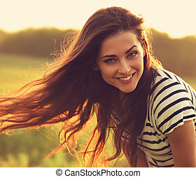 Beautiful smiling young woman looking happy with long amazing hair on nature bright sunset summer background. Closeup bright toned portrait