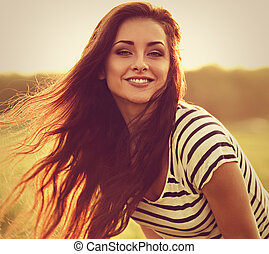 Beautiful smiling young woman looking happy with long amazing hair on nature bright sunset summer background. Closeup toned portrait