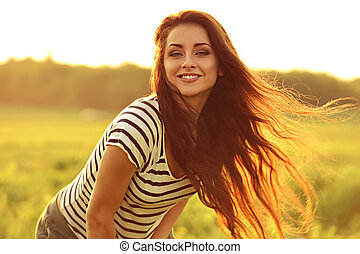 Beautiful smiling young woman looking happy with long amazing hair on nature bright sunset summer background. Closeup portrait
