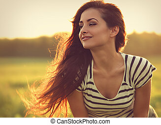 Beautiful smiling young woman looking happy with long amazing hair on nature bright sunset summer background. Closeup toned relaxing portrait