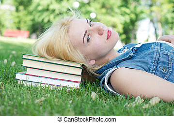 Beautiful smiling  young woman lying on grass and reading blue book, summer green park. Female student girl outside in park. Happy young university student of mixed European and Caucasian ethnicity.