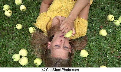 Beautiful smiling young woman lying on grass and bit taste apple fruit. 4K