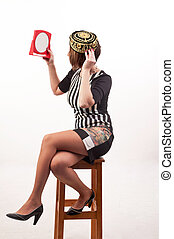 Beautiful smiling young woman trying a hat looking in mirror sitting on chair