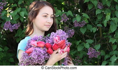 Beautiful smiling young woman with lilac flowers bouquet in hands outdoor