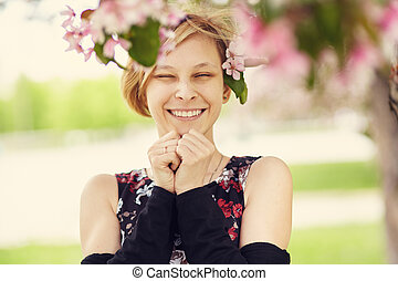 Beautiful smiling young woman with spring flowers in her hair.