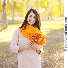 Beautiful smiling young woman with yellow maple leafs in autumn day