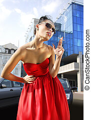beautiful smoking lady in red dress near business building