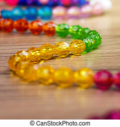 snake of colored beads on a wooden background