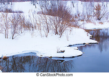 snow-covered river bank in winter