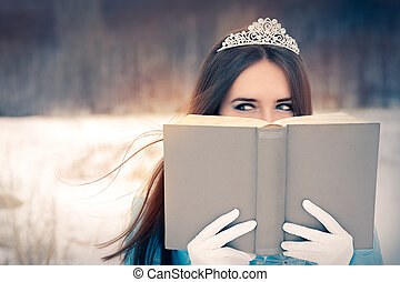 Portrait of a happy beautiful queen in royal dress reading a story book