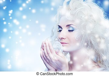 Beautiful snow queen with a christmas ball
