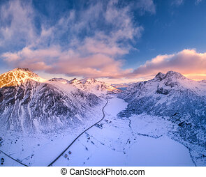 Beautiful snowy mountains in winter at sunset. Aerial view