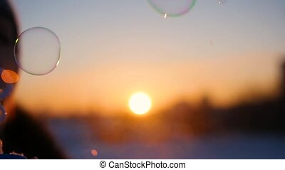 beautiful soap bubbles on background of sunset in winter frosty day
