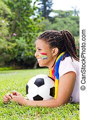 beautiful south african fan girl lying on field holding a soccer ball