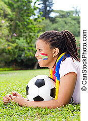beautiful south african fan girl lying on field holding a...