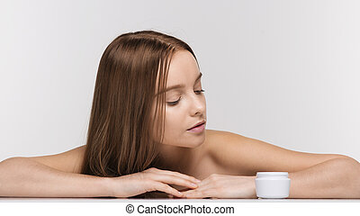 Beautiful spa girl with jar of cream isolated on white background