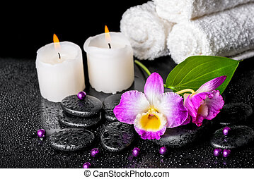beautiful spa still life of purple orchid dendrobium, leaf with dew, towels, candles and pearl beads on black zen stones, closeup