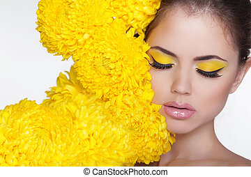 Beautiful Spa Woman over chrysanthemum flowers. Eyes makeup. Beauty Portrait. Perfect Fresh Skin. Pure Beauty Model Girl. Beautiful Face.