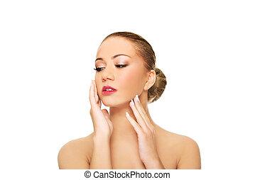 Beautiful spa woman touching her face.