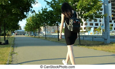 beautiful sport girl in a black dress and with a backpack walking down the street