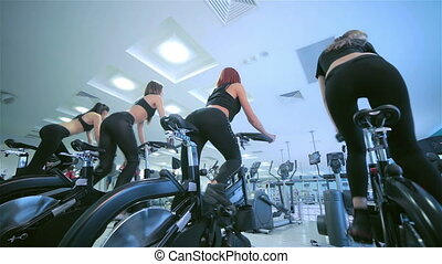 Beautiful sport on a stationary bike - A group of girls...