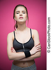 Beautiful sports woman standing with arms folded over pink background