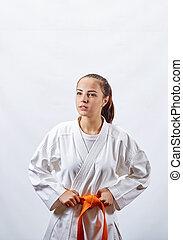 Beautiful sportswoman in karategi with an orange belt