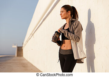 Beautiful sportswoman standing near wall with bottle and looking aside