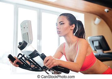 Beautiful sportswoman training on bicycle in gym