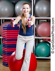 Beautiful sportswoman working out with dumbbells
