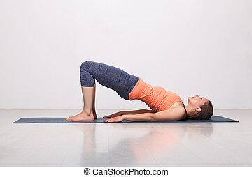 fit woman practices yoga asana setu bandhasana bridge pose