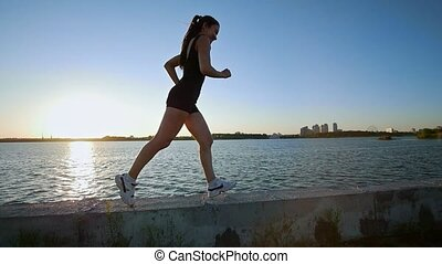 Beautiful Sporty Girl Running On The Waterfront, Slow Motion